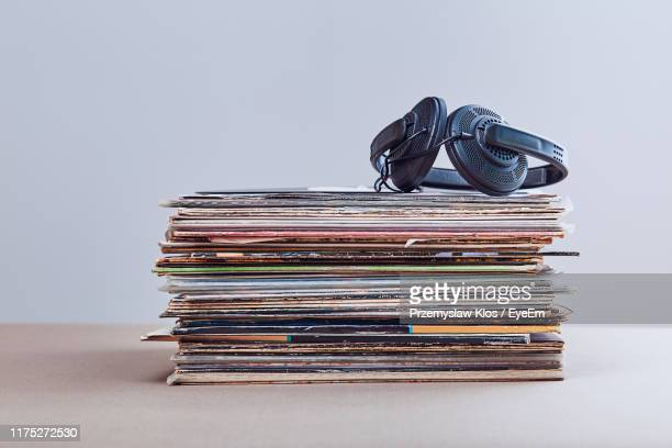 close-up of headphones on records at table against gray background - collection stock pictures, royalty-free photos & images