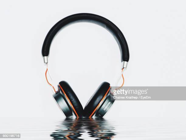 Close-Up Of Headphones Reflecting On Water Over White Background