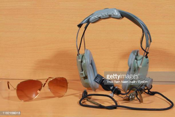 close-up of headset and aviator glasses on table - パイロットサングラス ストックフォトと画像