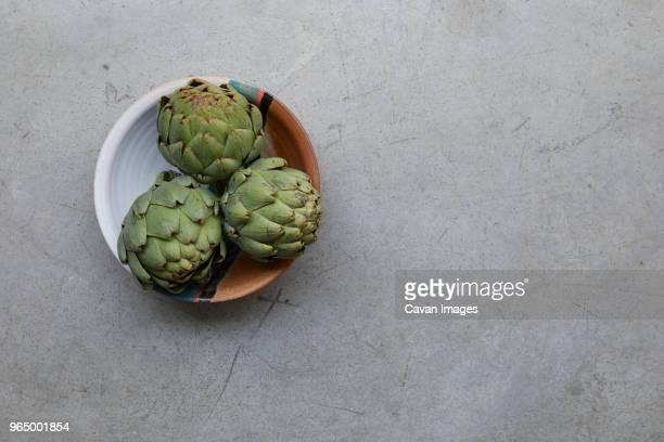 close-up of healthy artichokes in bowl on table - carciofo foto e immagini stock