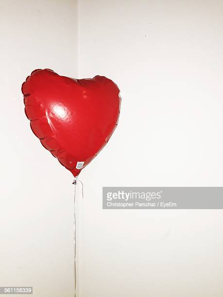Close-Up Of Heart Shape Balloon Over White Background