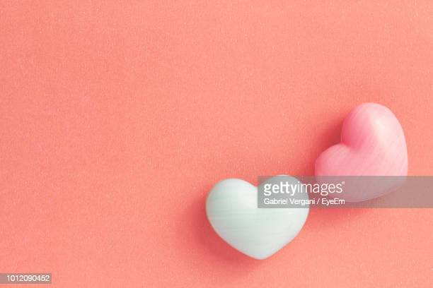 close-up of heart shape candies on coral table - candy heart stock pictures, royalty-free photos & images