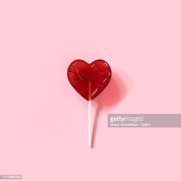 close-up of heart shape candy on pink background - lollipop stock pictures, royalty-free photos & images