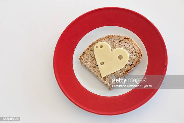Close-Up Of Heart Shape Cheese On Bread In Plate Against White Background