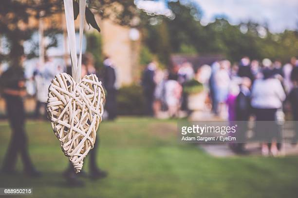 Close-Up Of Heart Shape Decoration With People In Background At Wedding Ceremony