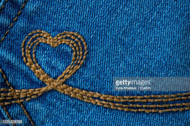 close-up of heart shape embroidery on jeans - embroidery stock pictures, royalty-free photos & images