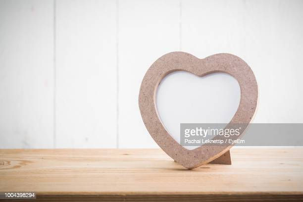 close-up of heart shape frame on wooden table against wall - photobylove stock pictures, royalty-free photos & images