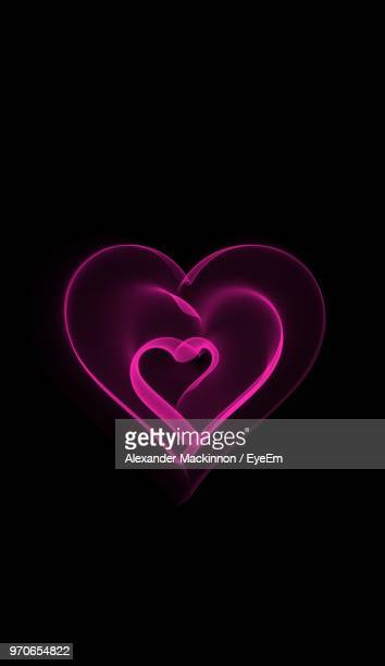 Close-Up Of Heart Shape Light Painting Over Black Background