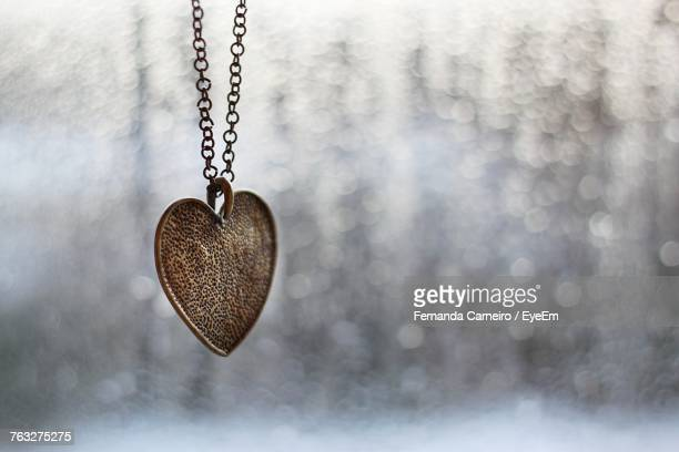 Close-Up Of Heart Shape Locket With Chain Hanging Against Blurred Background