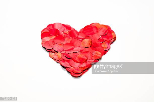 Close-Up Of Heart Shape Made With Red Sequins On White Background
