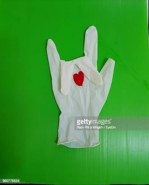 close-up of heart shape on white surgical glove over green table - green glove stock photos and pictures