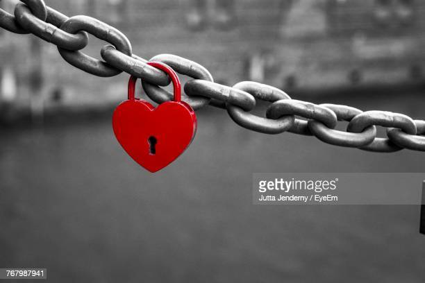 close-up of heart shape padlock hanging on chain - isolated color stock pictures, royalty-free photos & images