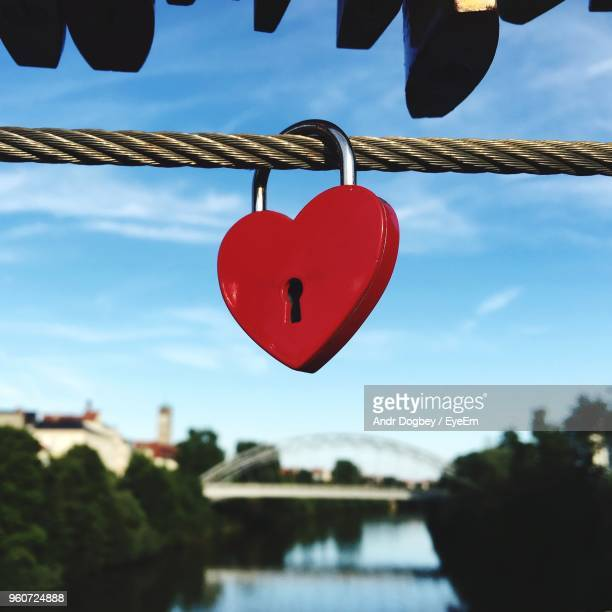 Close-Up Of Heart Shape Padlock Hanging On Rope Against Sky
