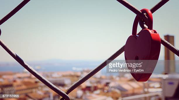 Close-Up Of Heart Shape Padlock On Chainlink Fence Against Sky During Sunny Day