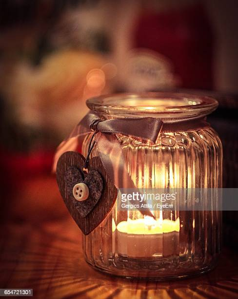 Close-Up Of Heart Shape Pendant Hanging On Jar With Burning Candle