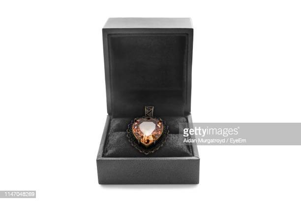 close-up of heart shape pendant in jewelry box on white background - ペンダント ストックフォトと画像