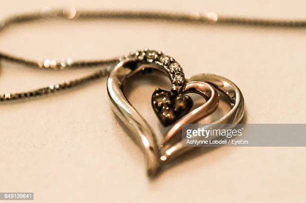 Close-Up Of Heart Shape Pendant Necklace On Table