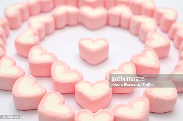 Close-Up Of Heart Shape Sweet Food Arranged Over White Background