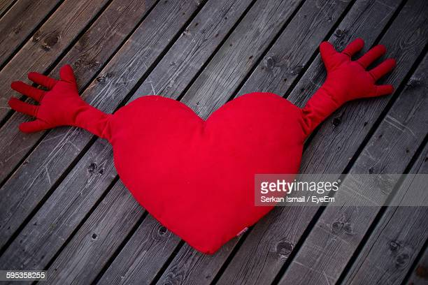 close-up of heart shape throw pillow on wooden table - cushion stock photos and pictures