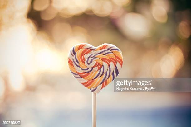 Close-Up Of Heart Shaped Lollipop Against Blurred Background