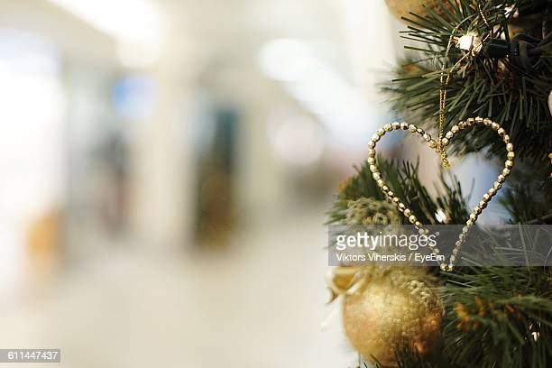 Close-Up Of Heart Shaped Object On Cropped Christmas Tree