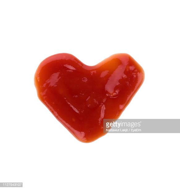 close-up of heart shaped sauce over white background - sauce stock pictures, royalty-free photos & images