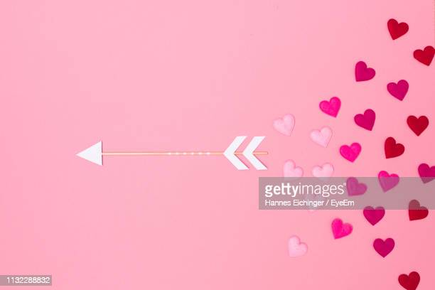 Close-Up Of Heart Shapes With Arroe Over Pink Background