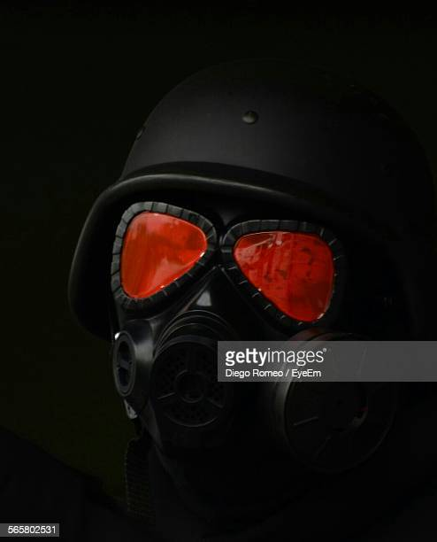 Close-Up Of Helmet And Gas Mask Against Black Background