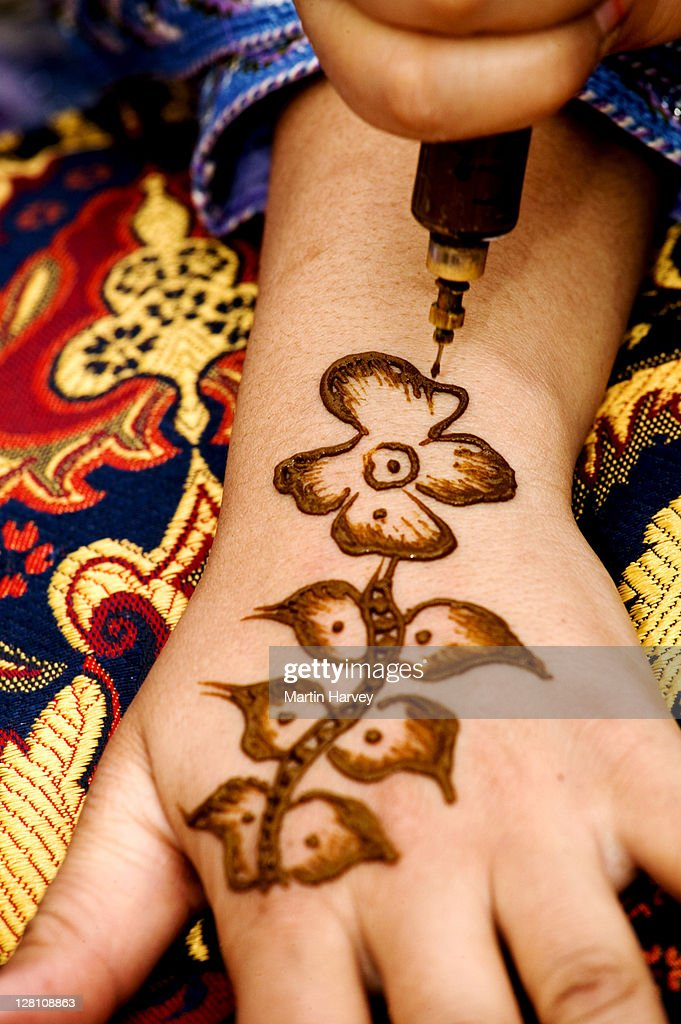 closeup of henna decorations being applied to henna powder is