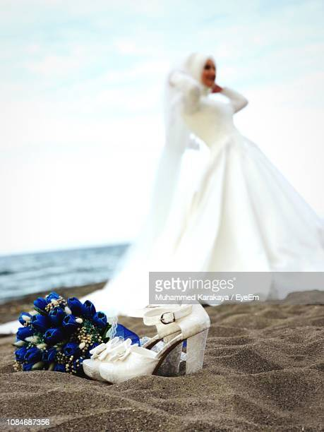 d2727e12c4a749 Close-Up Of High Heels With Bouquet Against Bride Standing At Beach