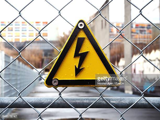 Close-Up Of High Voltage Sign Board On Chainlink Fence