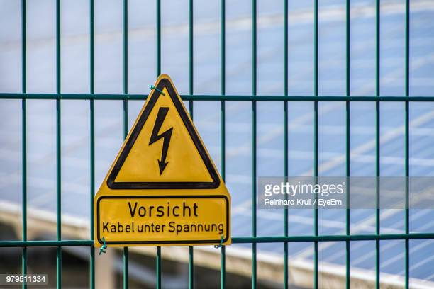 Close-Up Of High Voltage Sign On Fence