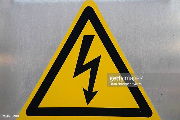 Close-Up Of High Voltage Sign On Wall