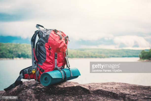 close-up of hiking backpack on rock by lake - rucksack stock-fotos und bilder