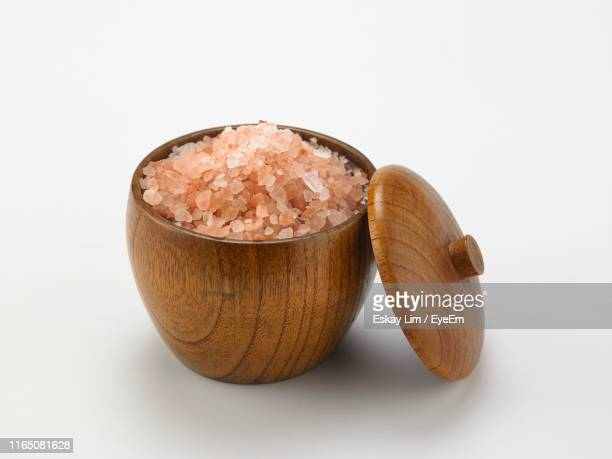 close-up of himalayan salt in wooden container over white background - himalayan salt stock pictures, royalty-free photos & images