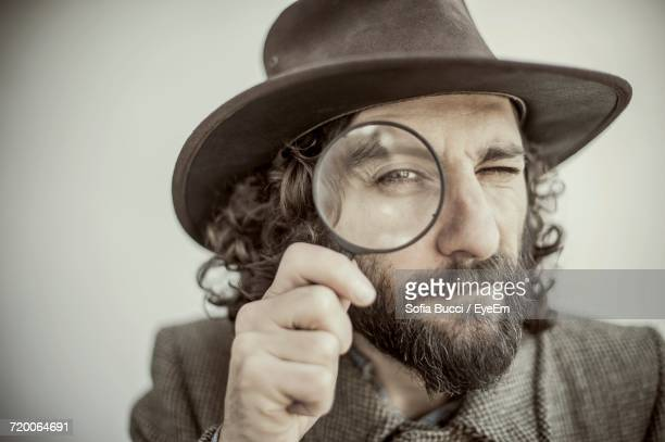 Close-Up Of Hipster Looking Through Magnifying Glass Against White Background