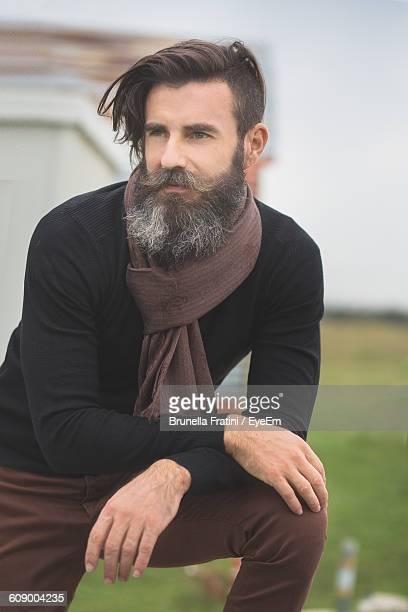 Close-Up Of Hipster On Field Against Sky