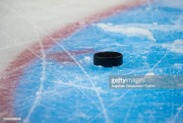 close-up of hockey puck in ice rink - hockey foto e immagini stock