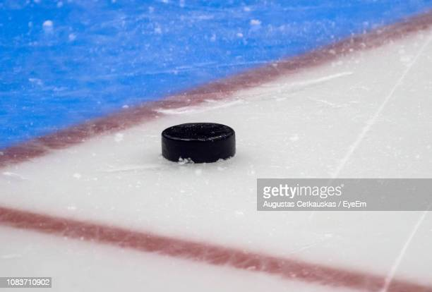 close-up of hockey puck on ice rink - ice hockey stock pictures, royalty-free photos & images