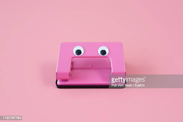 close-up of hole puncher with googly eyes against pink background - googly eyes stock pictures, royalty-free photos & images