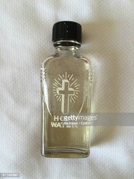 Close-Up Of Holy Water In Bottle On Fabric