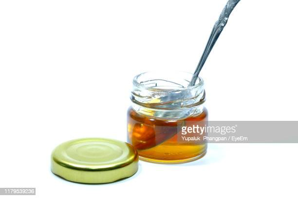 close-up of honey and spoon in jar against white background - jar stock pictures, royalty-free photos & images