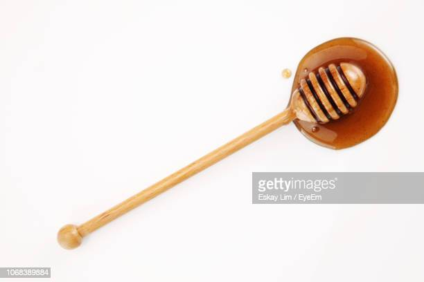 close-up of honey dipper over white background - honey stock pictures, royalty-free photos & images