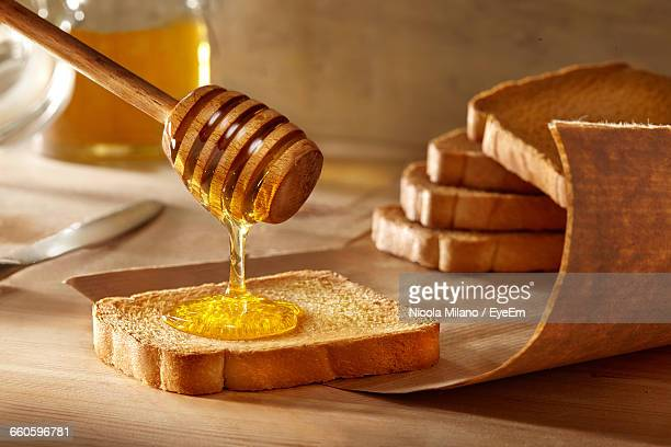 close-up of honey falling on bread from dipper - 蜂蜜 ストックフォトと画像