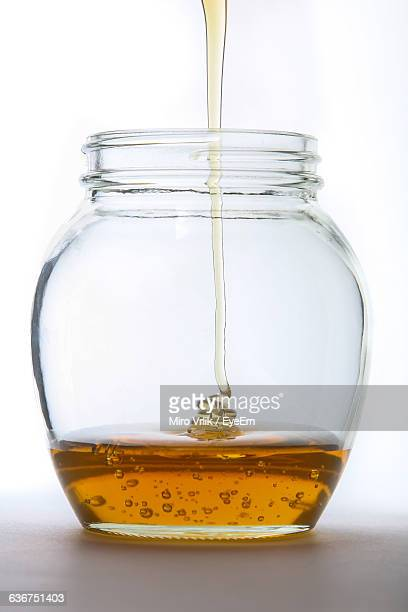 Close-Up Of Honey Pouring In Jar Against White Background
