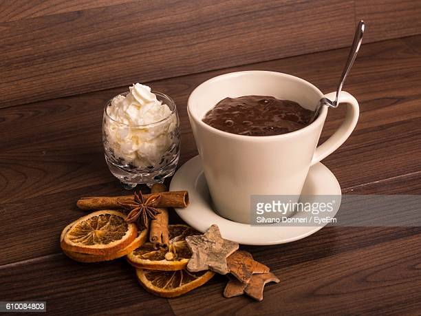 Close-Up Of Hot Chocolate With Cream And Spices On Table