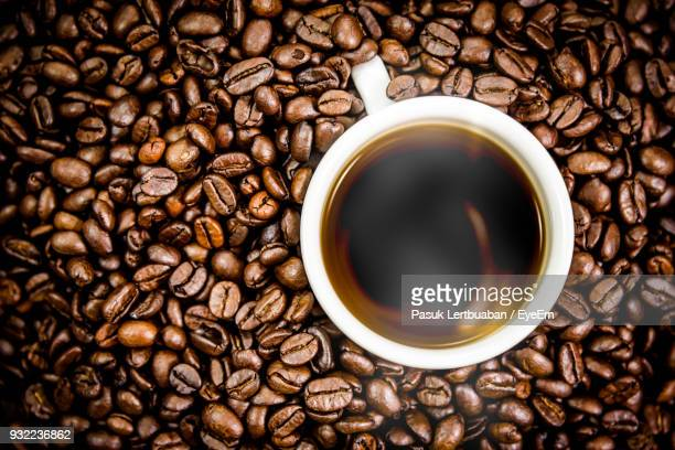 Close-Up Of Hot Coffee Amidst Beans