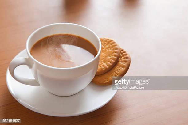 Close-up of hot tea and biscuits on table