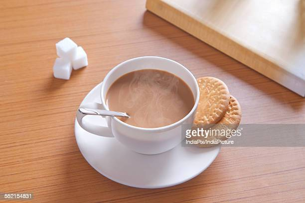 Close-up of hot tea, biscuits and sugar cubes on table