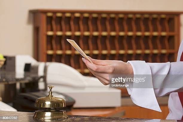 close-up of hotel receptionist holding key card